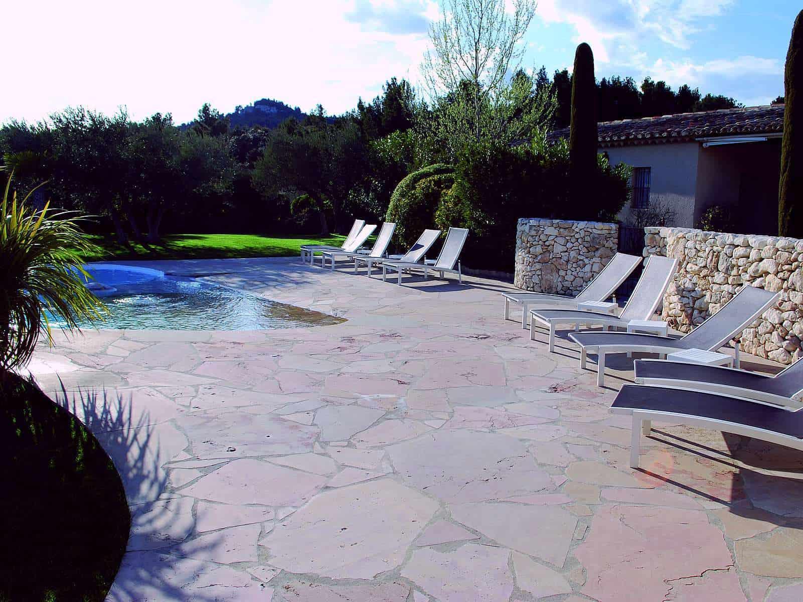 Hier sehen Sie eine mediterrane Kombination aus Toskana Bruchsteinplatten und einer Bruchsteinmauer aus einem Jurakalk-ähnlichen Gestein.