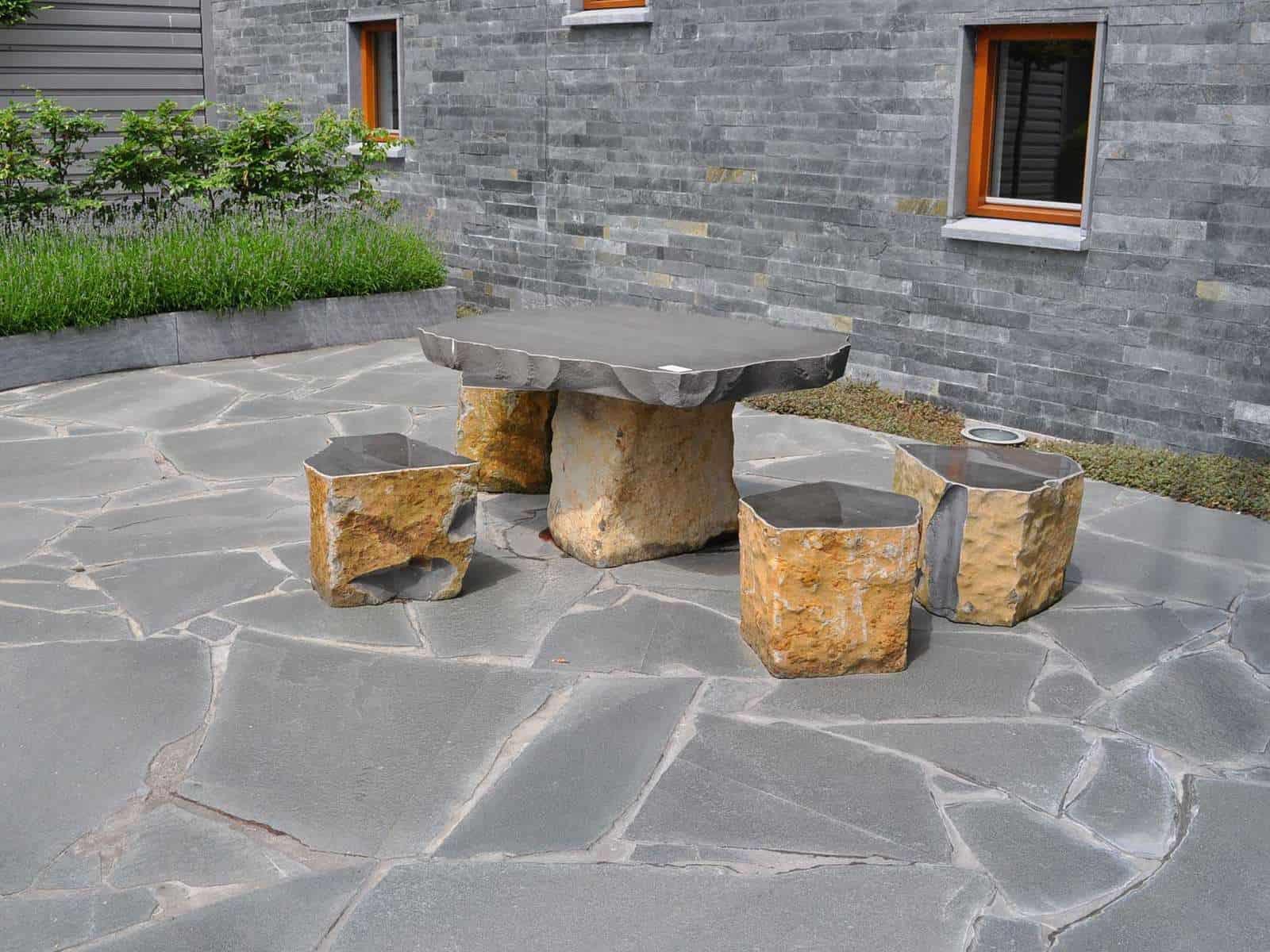 Terrasse mit großen Alta Quarzitplatten in Kombination mit Wandverblendern und einer Basalt Tischgruppe.